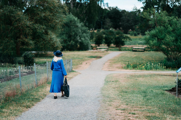 The Traveler - 2018 EyeEm Awards The Great Outdoors - 2018 EyeEm Awards Old Senior Lady Hat Dress Woman Blue Full Length Tree Women Walking Sky Walking Cane Empty Road Hiking Pole Road Leading Mountain Road The Way Forward