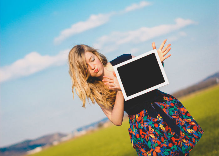 Young woman using smart phone against sky