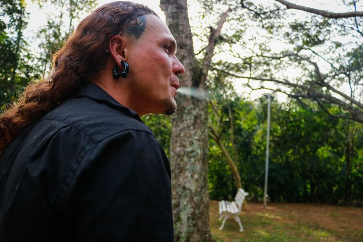 Man with long hair exhaling smoke against trees in forest