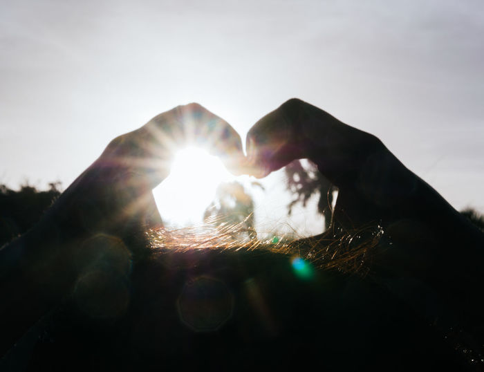 Silhouette of a person's hand making a heart shape. Hands Beauty In Nature Close-up Day Hand Heart Shape Human Body Part Human Hand Leisure Activity Lens Flare Lifestyles Nature One Person Outdoors Personal Perspective Real People Sky Sun Sunbeam Sunlight Unrecognizable Person