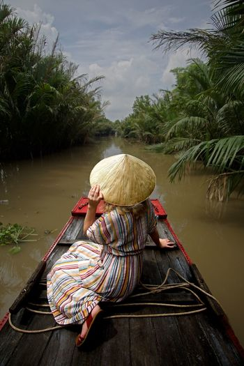 Rear view of woman sitting in boat against sky