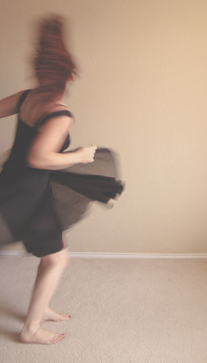 Side view of woman dancing against wall at home