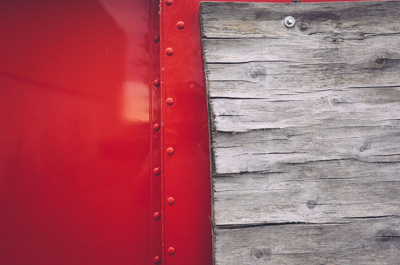 Close-up of red door on wooden cabin