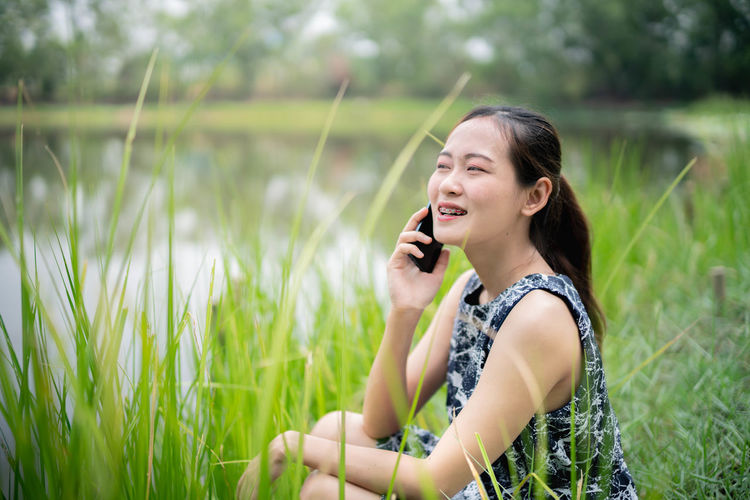 One Person Young Adult Holding Happiness Plant Leisure Activity Talking Real People Smiling Technology Grass Telephone Young Women Field Using Phone Communication Casual Clothing Nature Day Women Wireless Technology Beautiful Woman Hairstyle Outdoors