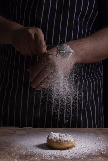 Midsection Of Man Sifting Powdered Sugar On Donut