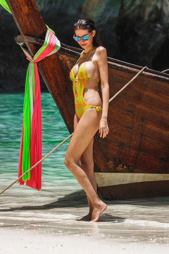 Woman model in a yellow bikini posing next to a thai long tail boat in Maya Bay, Phi Phi Leh, Thailand Maya Beach Thai Thailand Vacations Beach Beautiful Woman Boat Fashion Glasses Hairstyle Holding Island Leisure Activity Lifestyles Longtail Boat Model One Person Outdoors Phi Phi Island Real People Sunglasses Young Adult Young Women
