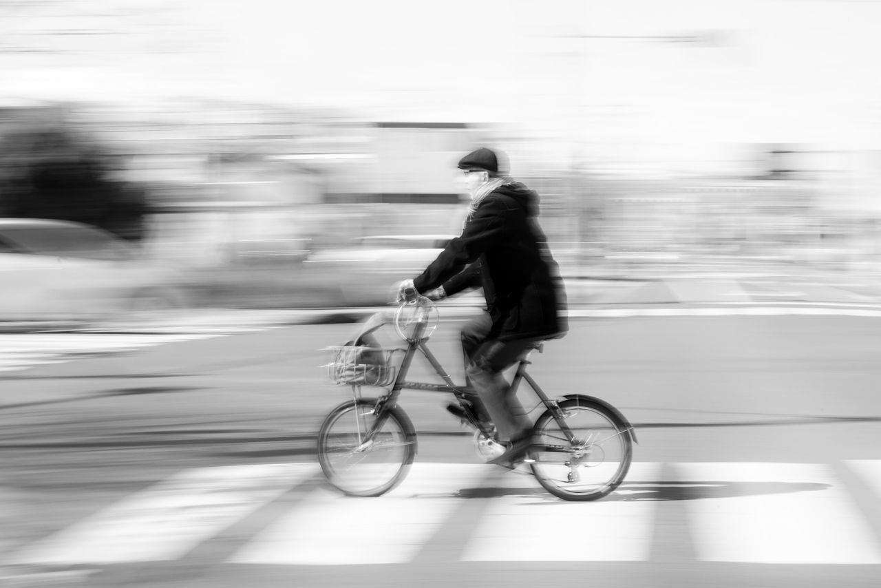 blurred motion, real people, motion, transportation, speed, one person, full length, bicycle, men, land vehicle, riding, side view, road, outdoors, day