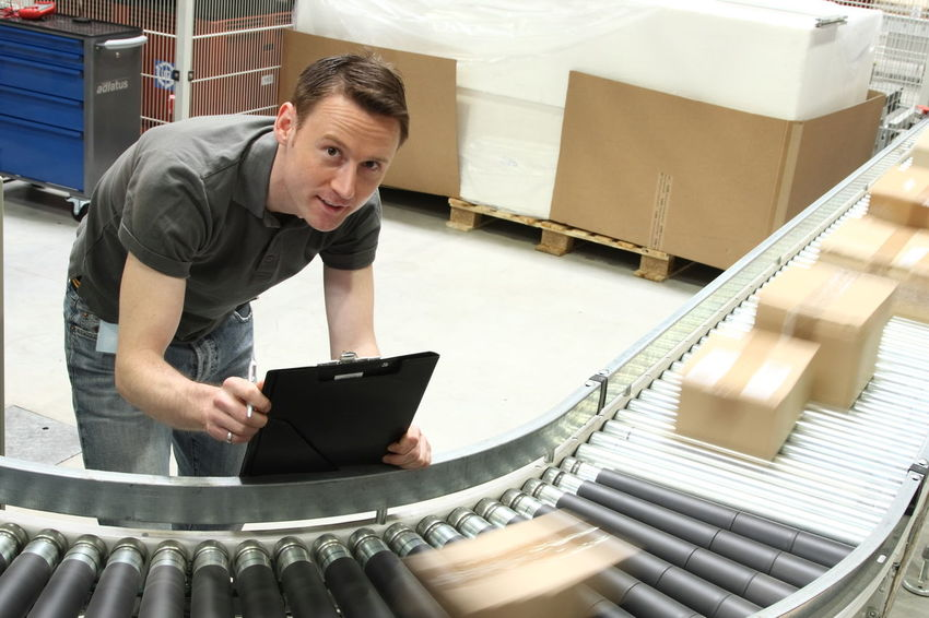 Warehouse worker with conveyor belt and parcels. At Work Box Conveyor Belt Delivery Delivery Service Industrial Industry Logistics Worker Conveyor  Indoors  Job Men Occupation One Person Only Men Parcel People Standing Warehouse