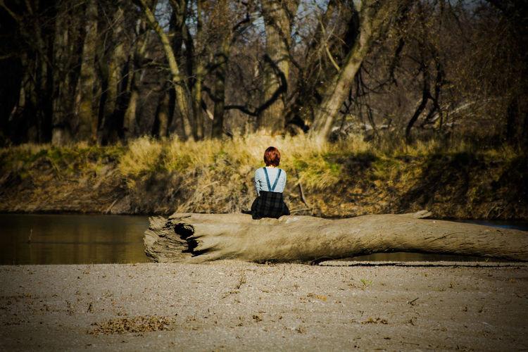 Woman sitting on log against trees