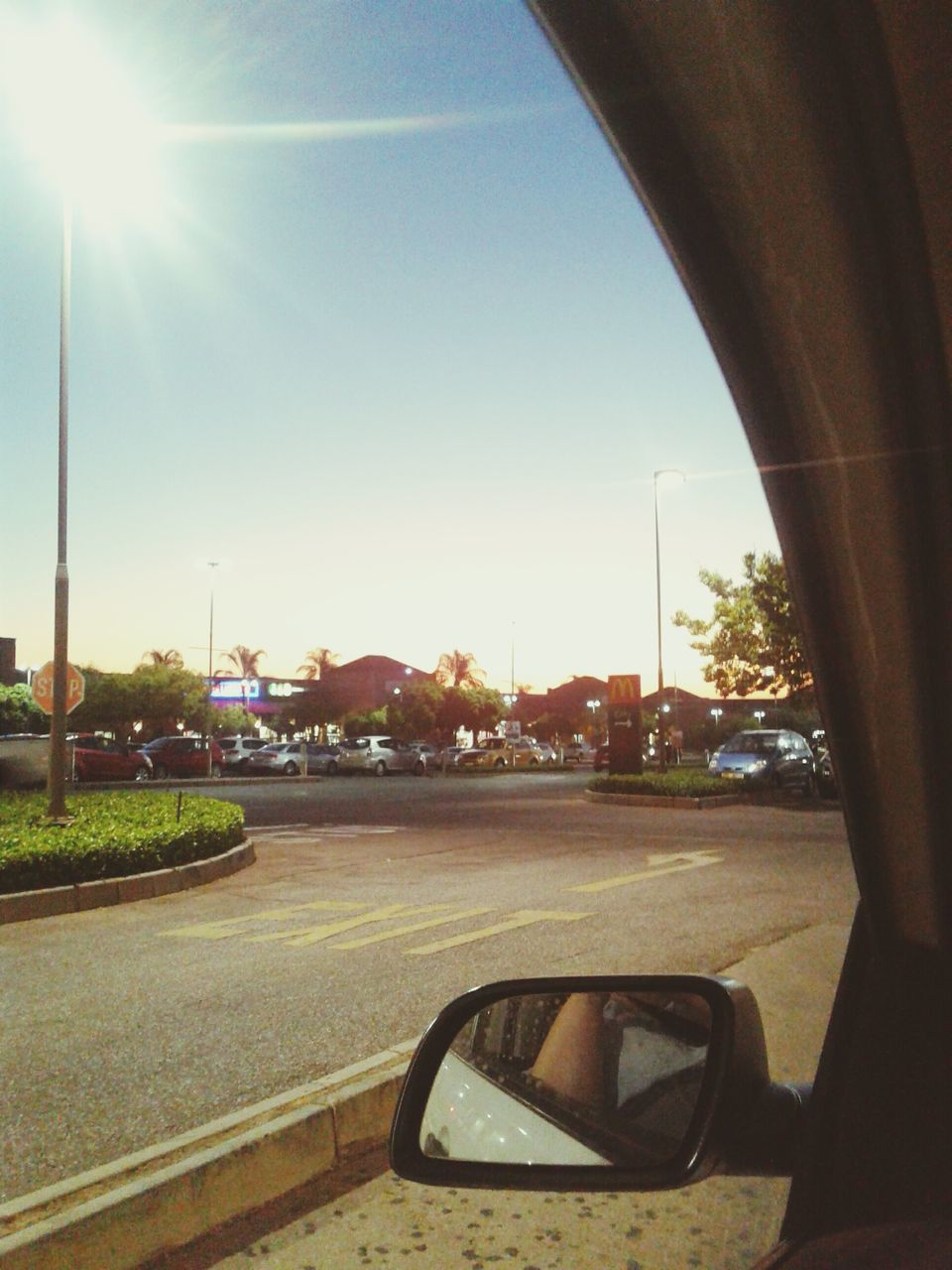 transportation, car, road, sky, land vehicle, sun, sunlight, side-view mirror, mode of transport, car interior, tree, clear sky, sunset, no people, day, outdoors, nature, city, close-up