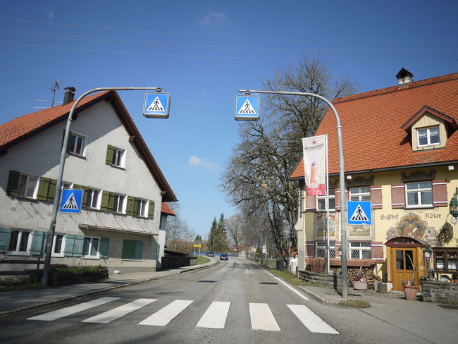 Trafficsign in south Germany Allgäu Guiding Traffic Architecture Building Exterior Built Structure Clear Sky Day Guidance Guide House No People Outdoors Residential Building Road Road Sign Sky Street The Way Forward Traffic Sign Transportation Tree