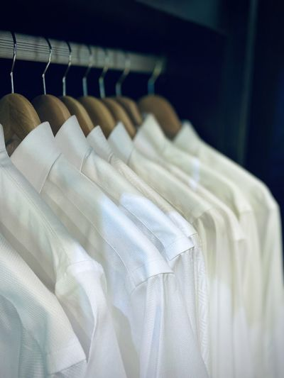 Close-up of white shirts hanging in closet