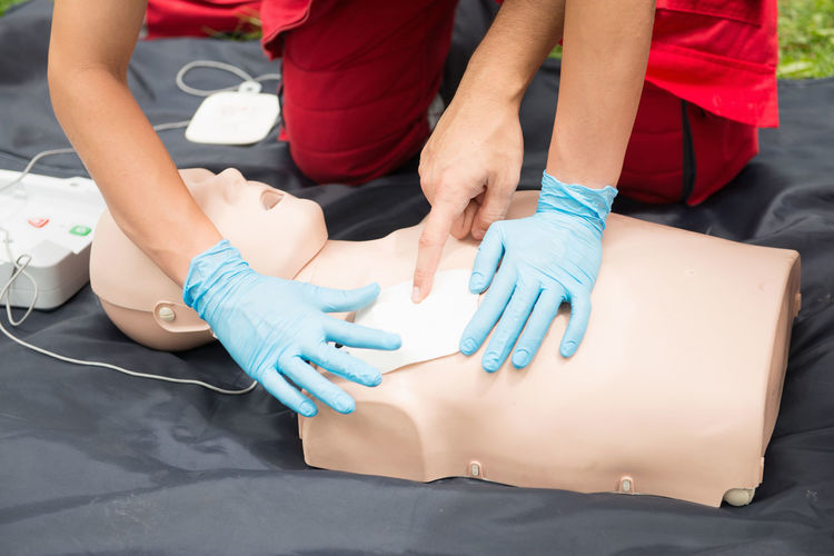 Cropped hand of man instructing while paramedic practicing cpr on dummy