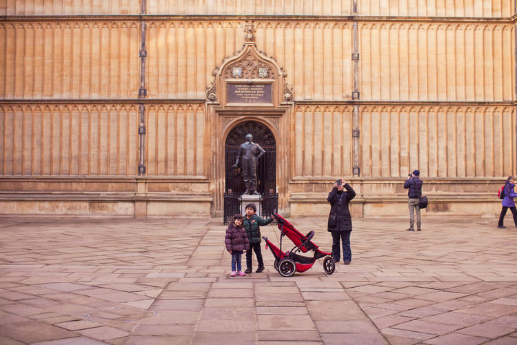 Tourist amazed by the beautiful building near Oxford Oxford Adult Architecture Baby Stroller Building Exterior Built Structure Child Childhood City Day Full Length Outdoors People Togetherness Two People Walking Women Stories From The City Stories From The City