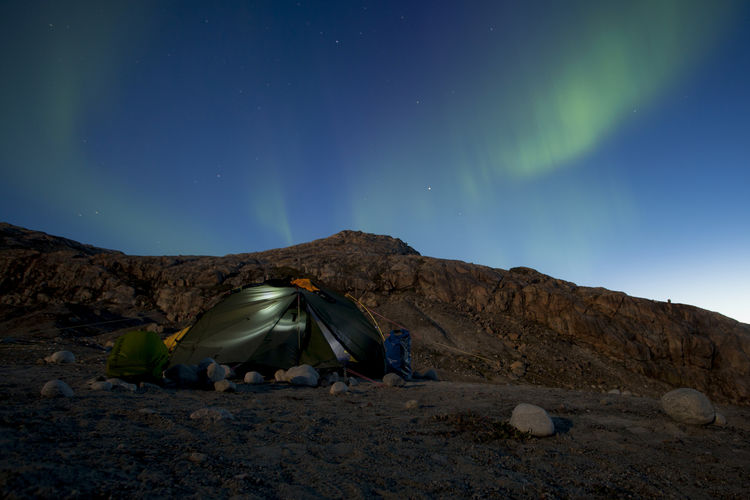 Side view of tent on mountain against sky at night