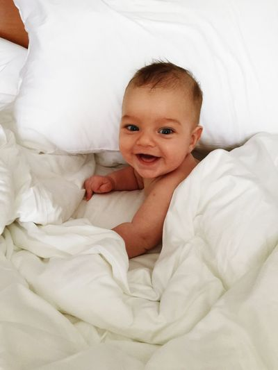 Portrait Of Cute Baby Boy On Bed At Home