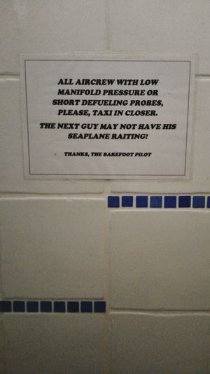 Bathroom warning in men's side Plane Relaxing Taking Photos