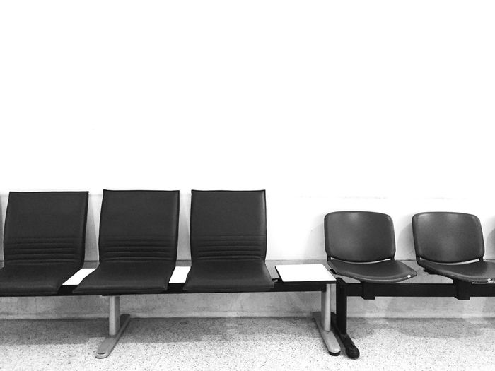 Empty chairs in row against wall
