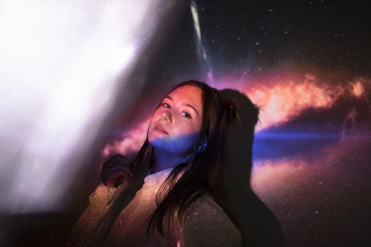 Portrait of beautiful woman standing at night