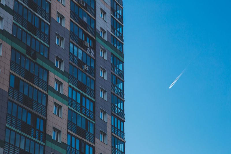 Falling plane Apartment Architecture Blue Building Building Exterior Built Structure Business City Clear Sky Day Low Angle View Modern Nature No People Office Office Building Exterior Outdoors Residential District Sky Sunlight Window