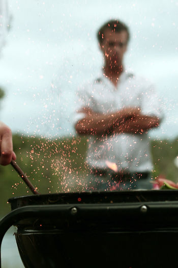 Close-up of hand preparing food on barbecue