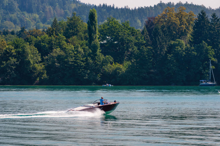 WORTHERSEE, AUSTRIA - AUGUST 08, 2018: View from the boat to the lake and coastline. Local residents and tourists swim, driven by motorboats and use other forms of water recreation. Nature Day Outdoors Austria Carinthia Carinthian Lakes Tourist Tourists Lake Wörthersee Recreation  Leisure Landscape Water Sea Boats Motorboat Speedboats Summer People Holidays Fun Travel Beach Resort Lifestyle Sunny Rest Joy Waves Europe Alps Alpine Alpine Lake Nautical Vessel Transportation Mode Of Transportation Tree Waterfront Plant Men Motion Real People Beauty In Nature Leisure Activity Lifestyles