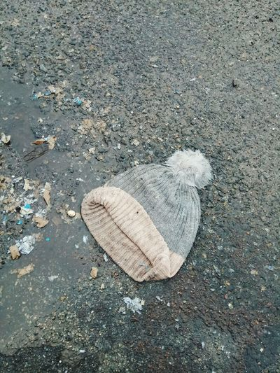 Booble laying in the dirt Street Dirt Bobble Hat  Christmastime Seasonal Season  Winter Wintertime Garbage Pollution Clothing Documentary Depression - Sadness Depressed Tristesse Textured  Heart Shape Pebble