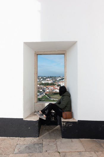 Woman sitting on wall of building