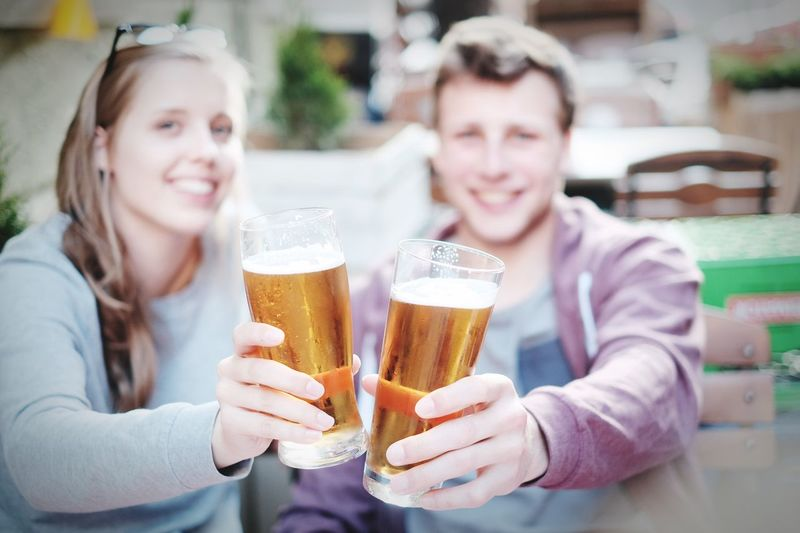 Portrait of young friends holding beer glasses at bar