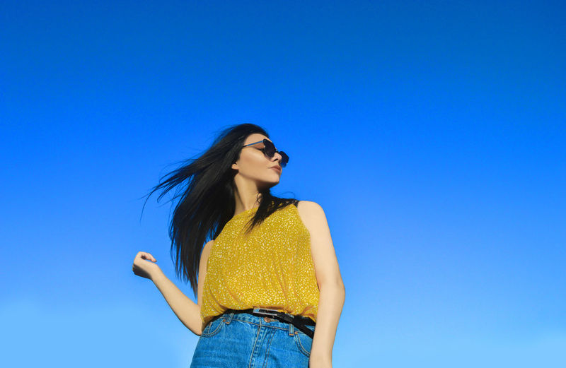 Low angle view of young woman standing against clear blue sky