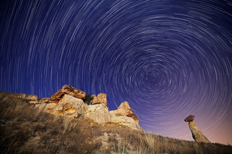 Low angle view of star trail over mountain against sky at night