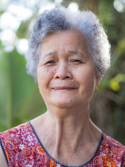 Portrait of elderly woman with short white hair standing smiling and looking the camera in garden.