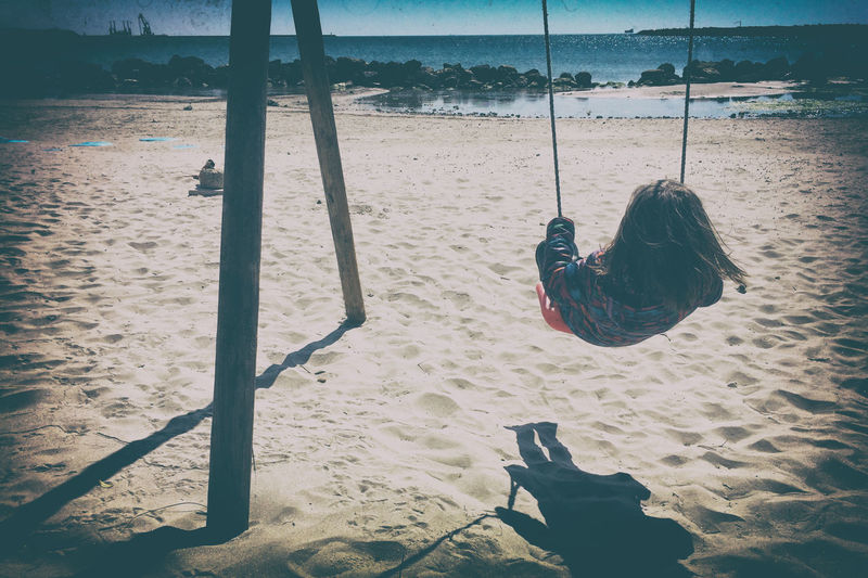 Rear view of girl swinging at beach on sunny day