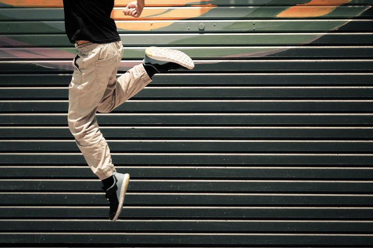 Low Section Of Man Jumping Against Shutter
