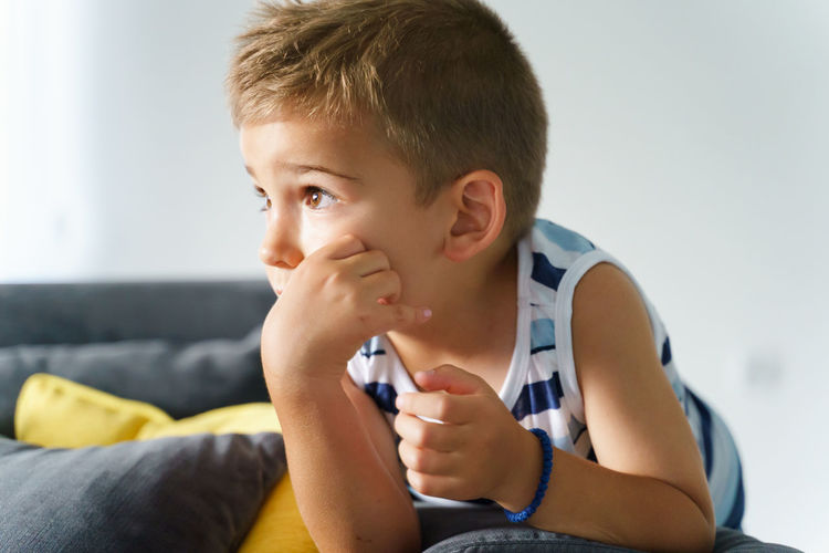 Boy looking away while sitting on sofa