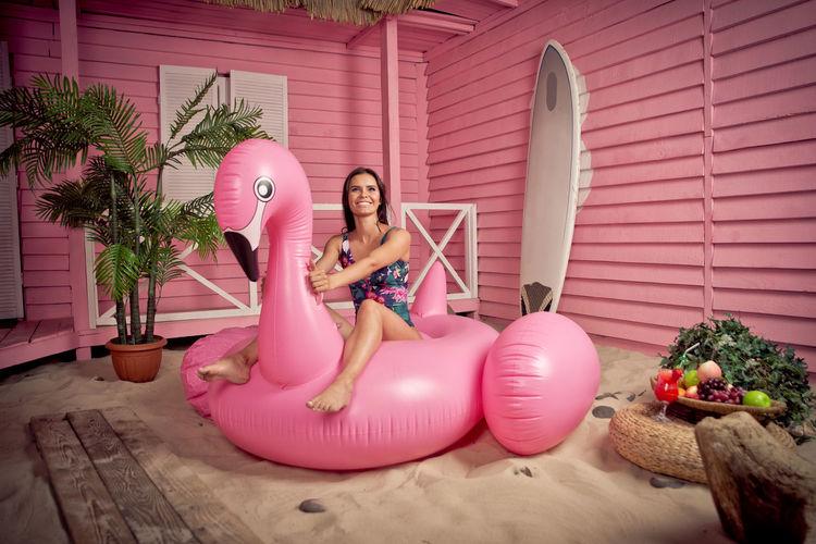 Full length of woman wearing bikini sitting on pool raft at beach
