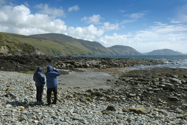 Rear view of friends standing on shore against sky
