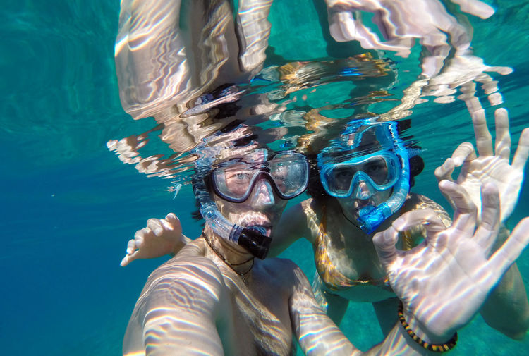 Couple showing ok sign while snorkeling in sea