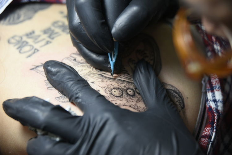 Cropped hand of artist drawing tattoo on customer body