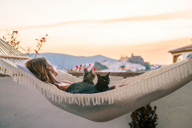 Woman with cats relaxing on hammock against sky during sunset
