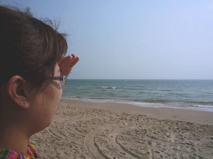 Woman shielding eyes at beach against clear sky