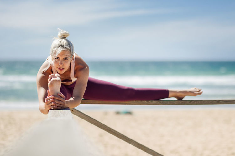 Caucasian woman practicing yoga at seashore. Young female stretching legs in the beach in Cadiz, Andalusia, Spain. Water Sea One Person Sky Horizon Over Water Horizon Nature Lifestyles Leisure Activity Day Holding Adult Real People Women Land Beach Sitting Holiday Outdoors
