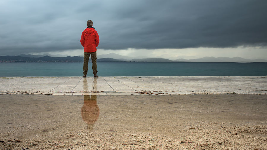 Man standing on promenade while looking at sea during stormy weather
