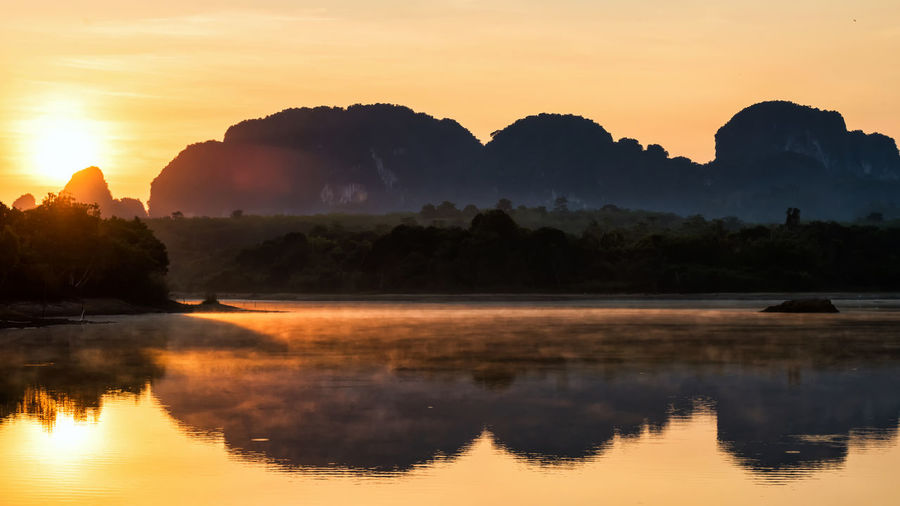 Limestone mountains and motion fog or mist over lake in sunrise, nong thale, krabi, thailand.