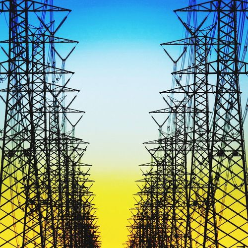 Energy. Symmetry Electricity Pylon Silhouette Sky No People Nature Day Steel Outdoors Clear Sky Milko Marchetti Photographer Photooftheday Power Energy Yellow Blue Sky Blue First Eyeem Photo