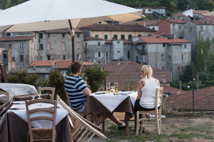Rear view of couple sitting at outdoor restaurant