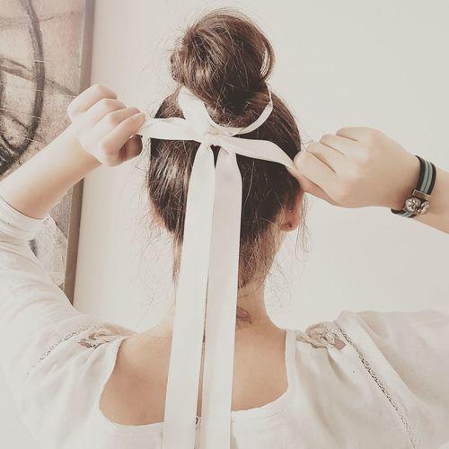 Rear view of bride tying ribbon on hair bun
