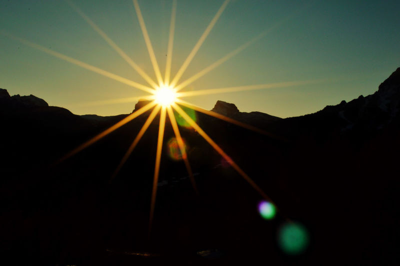 Sun shining over silhouette mountain against sky during sunset
