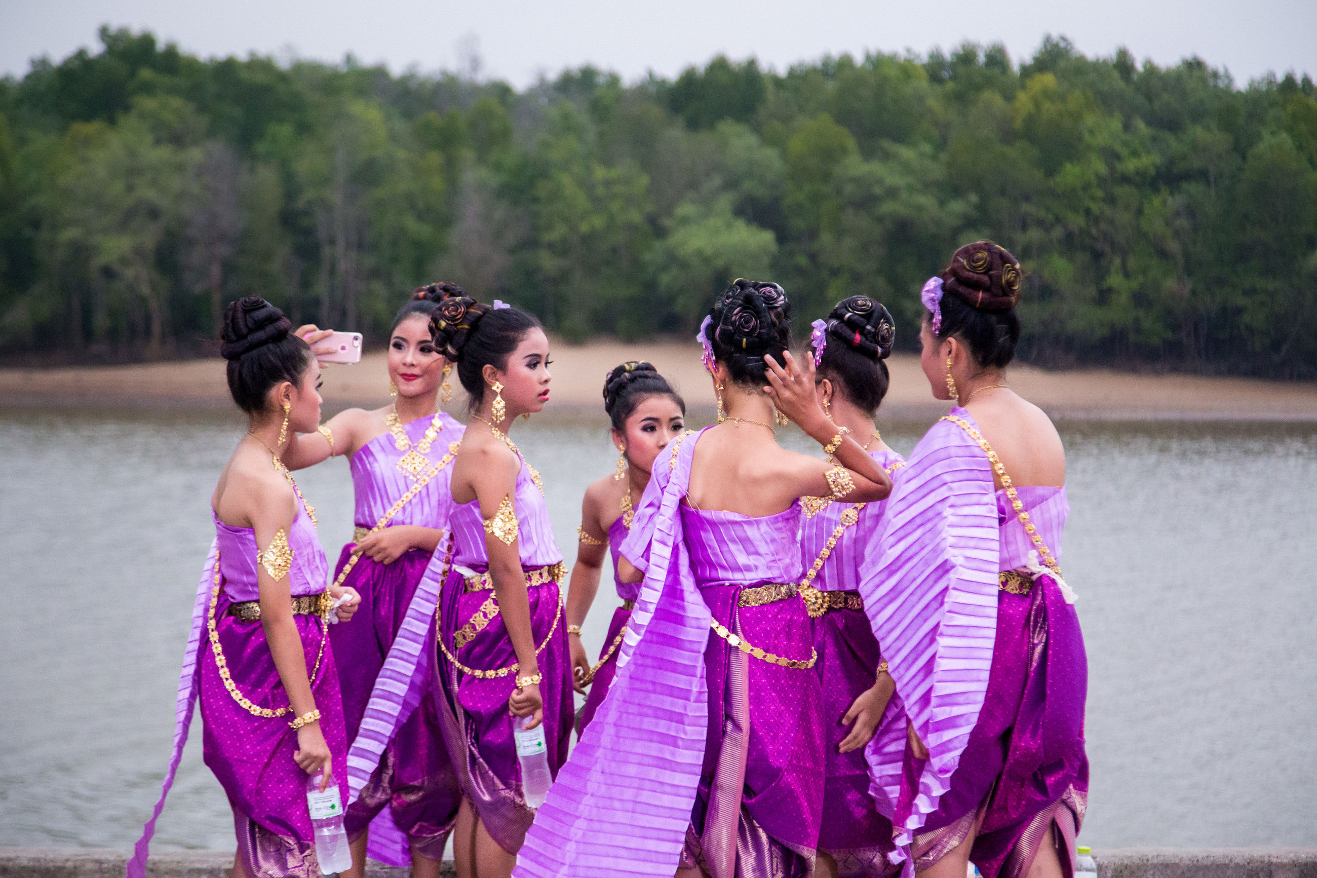 water, women, real people, group of people, togetherness, three quarter length, adult, standing, nature, pink color, traditional clothing, people, day, lifestyles, clothing, event, celebration, holding, leisure activity, outdoors, purple, positive emotion, couple - relationship