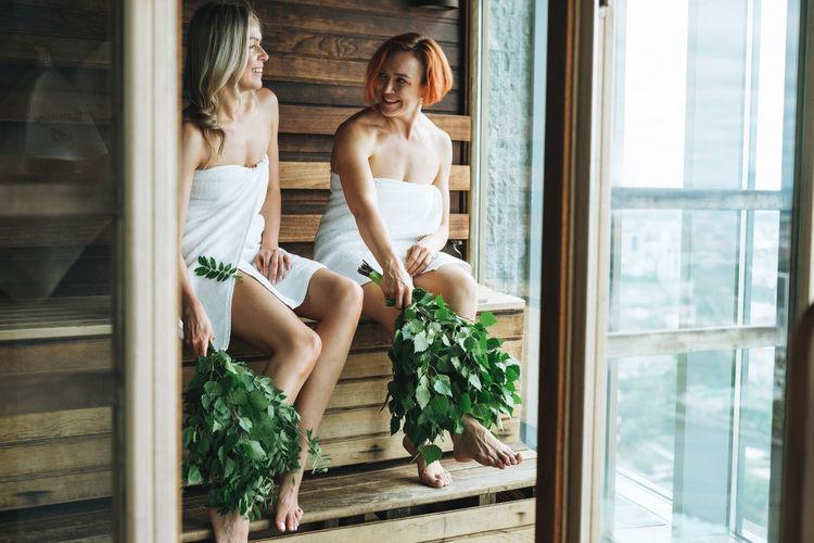 Young women in white towel sitting on wooden shelf in finnish sauna russian bath with rowan brooms
